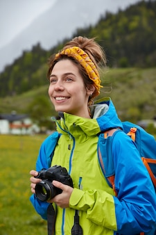 La donna europea spensierata sorridente tiene la macchina fotografica professionale, guarda positivamente in lontananza