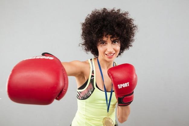 Smiling carefree sports woman boxing at the camera