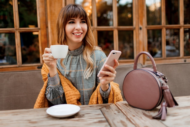 Smiling carefree  woman have a coffee break in cozy cafe with wood interior , using mobile phone. holding cup of hot cappuccino. winter season.