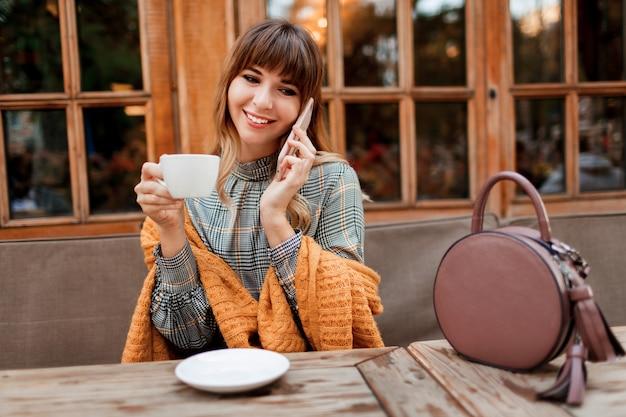 Sorridente donna spensierata ha una pausa caffè in un accogliente bar con interni in legno, utilizzando il telefono cellulare. tenendo la tazza di cappuccino caldo. stagione invernale.
