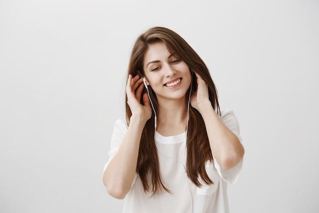 이어폰에 평온한 여자 듣기 음악 미소