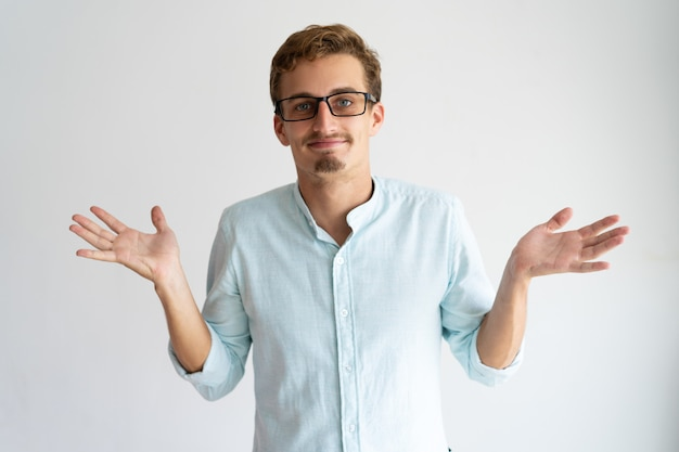 Smiling careless blonde guy showing do not know gesture.