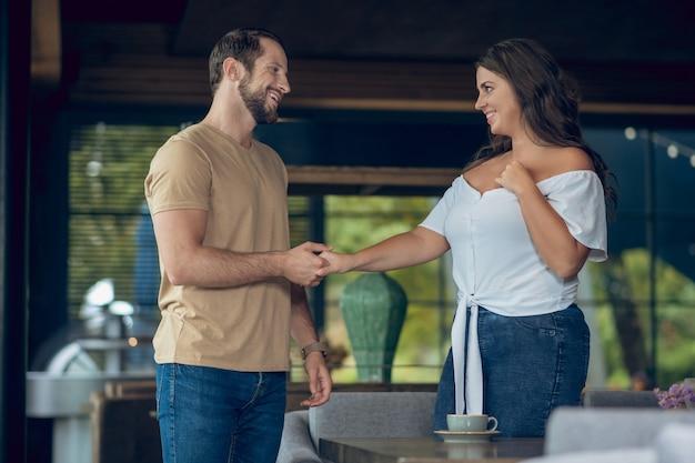 カフェのテーブルに座っている長い髪の楽しい女性の肩を抱き締める思いやりのある男の笑顔