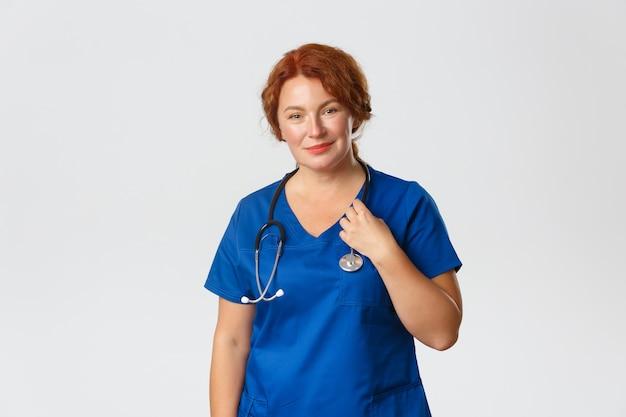 笑顔の思いやりのある中年赤毛の医者、聴診器笑顔で青いスクラブで女性医師、病院で患者を治療、のために人々をテスト、立っている灰色の壁