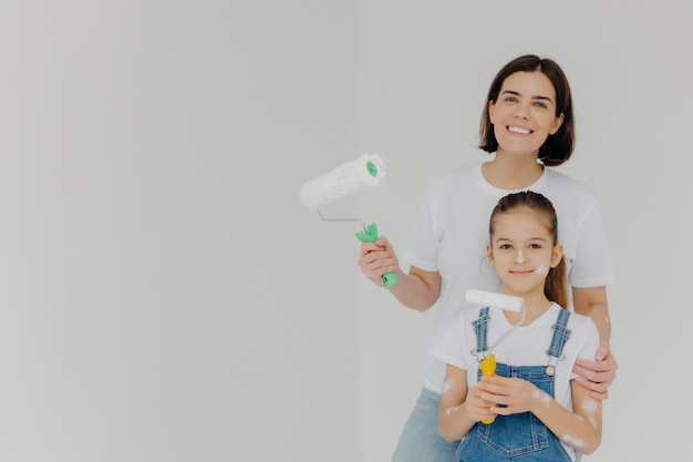 Smiling caring mother embraces daugher, stands with paint rollers