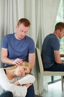 彼の膝の上で頭を休んでいる彼のガールフレンドにリラックスしたヘッドマッサージを与える笑顔の思いやりのある若い男