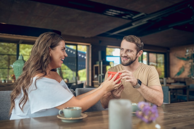 Smiling caring young man with gift and ecstatic surprised woman sitting at table in cafe