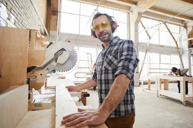 Smiling carpenter cutting wood