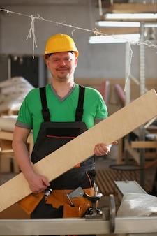 Smiling carpenter holding wood