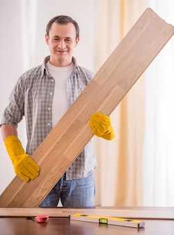 Smiling carpenter in rubber gloves holding wooden planks.