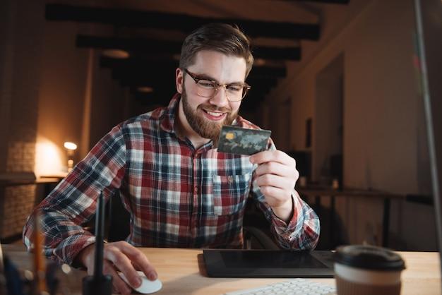 Улыбающийся случайный деловой человек, оплачивающий онлайн с помощью своей кредитной карты в офисе