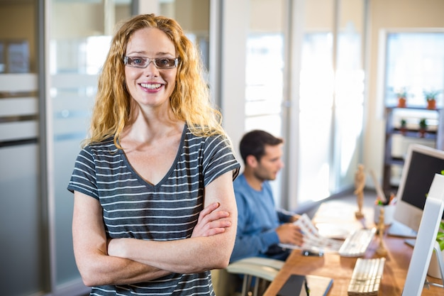 Smiling casual businesswoman posing with her partner behind in the office