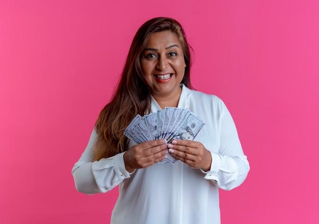 Улыбающаяся повседневная кавказская женщина средних лет, держащая деньги на розовом