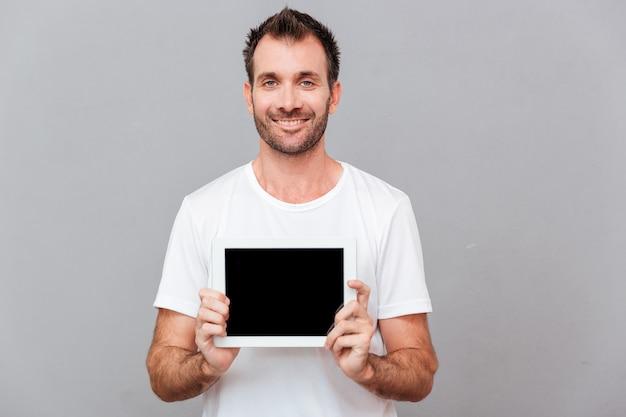 Улыбающийся случайный человек, показывающий пустой экран планшетного компьютера на сером фоне