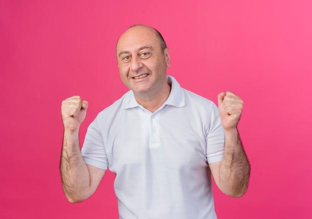 ピンクの背景で隔離のカメラを見てはいジェスチャーをしているカジュアルな成熟したビジネスマンの笑顔