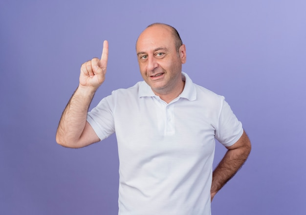 Smiling casual mature businessman keeping hand behind back and raising finger isolated on purple background