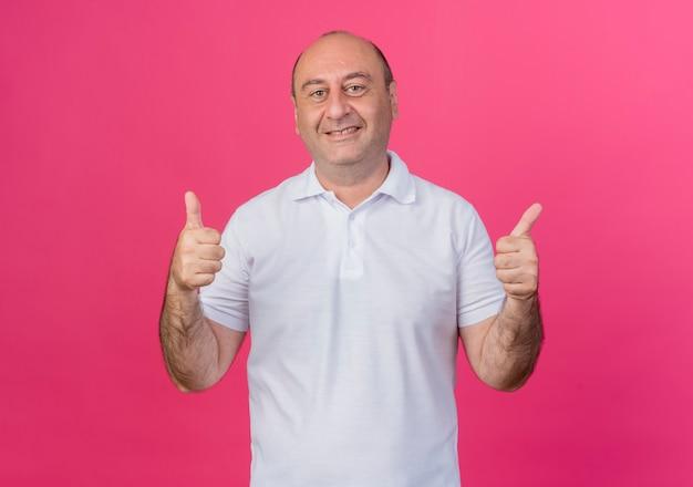 복사 공간 분홍색 배경에 고립 엄지 손가락을 보여주는 캐주얼 성숙한 사업가 미소