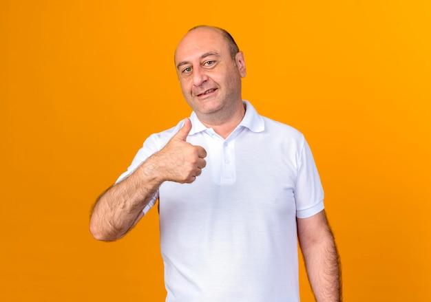 黄色の壁に分離された彼の親指を上に笑顔