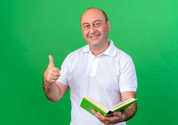 Улыбающийся случайный зрелый мужчина, держащий книгу большим пальцем вверх, изолирован на зеленой стене
