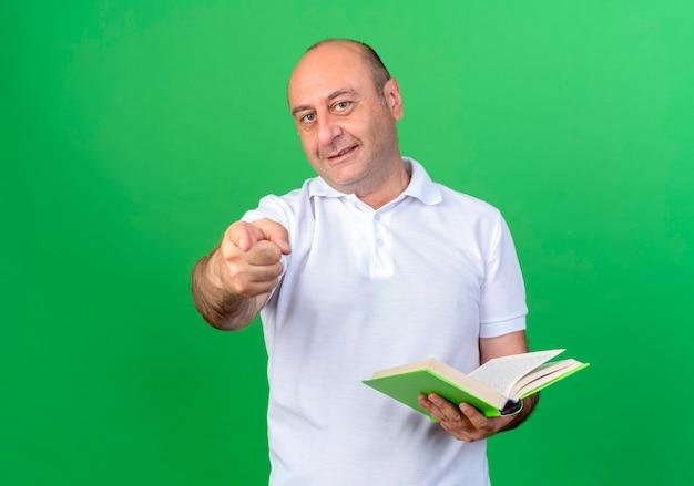 Sorridente casual uomo maturo che tiene il libro e mostrandoti gesto isolato sulla parete verde