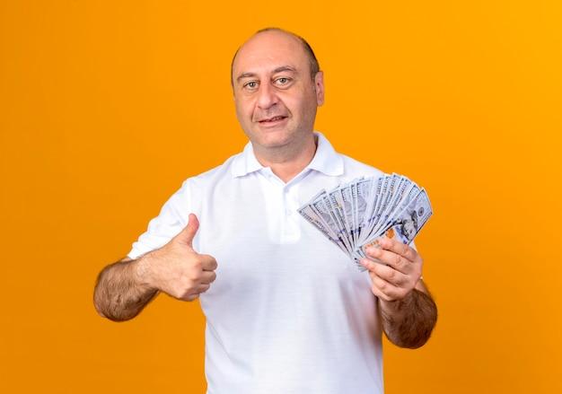 黄色の壁に分離された現金と彼の親指を保持しているカジュアルな成熟した男
