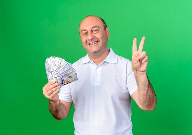 現金を保持し、緑の壁に分離された平和のジェスチャーを示す笑顔のカジュアルな成熟した男