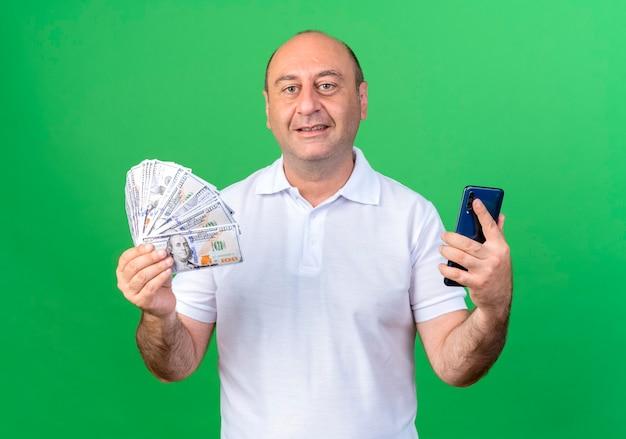 Uomo maturo casuale sorridente che tiene contanti con il telefono isolato sulla parete verde