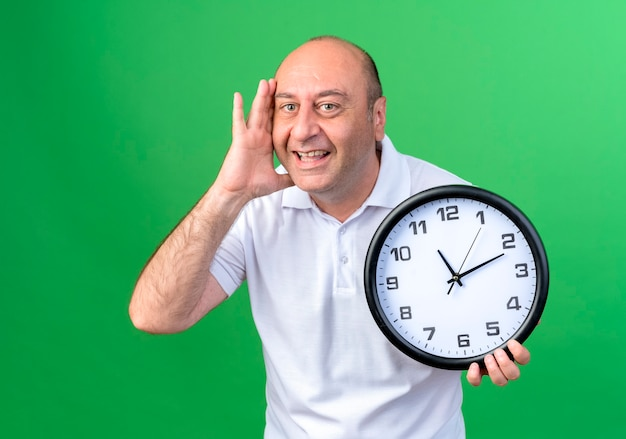 Sorridente casual uomo maturo tenendo l'orologio da parete e mettendo la mano sulla guancia isolata sulla parete verde