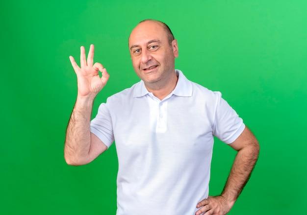 Uomo maturo casuale sorridente che mostra il gesto okey e che mette la mano sull'anca isolata sulla parete verde