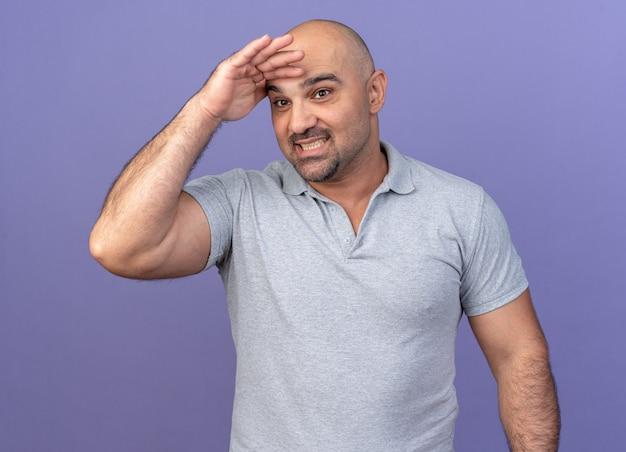 紫色の壁に隔離された距離に横を見て額に手を保持しているカジュアルな中年男性の笑顔