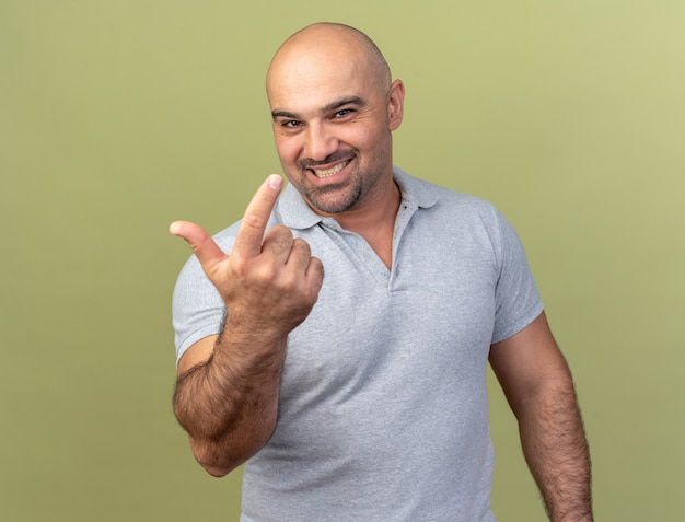 Smiling casual middle-aged man looking at front doing loser gesture isolated on olive green wall