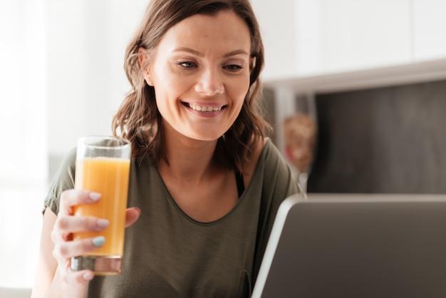 カジュアルな女性がジュースを飲むとキッチンでタブレットコンピューターを使用して笑顔