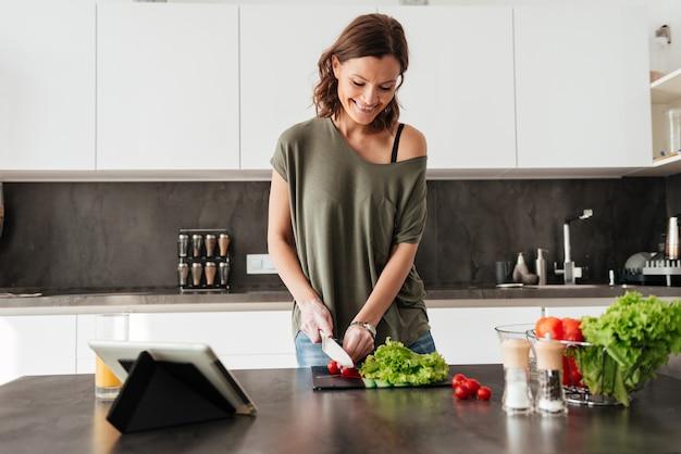 Smiling casual woman making fresh salad