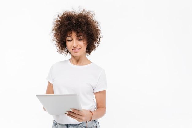 立っているとタブレットコンピューターを使用してカジュアルな女性の笑顔