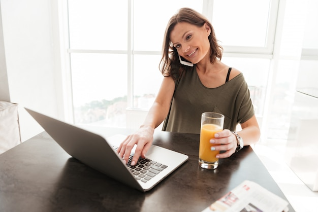 Smiling casual woman talking on smartphone, using laptop computer and drinking juice by the table
