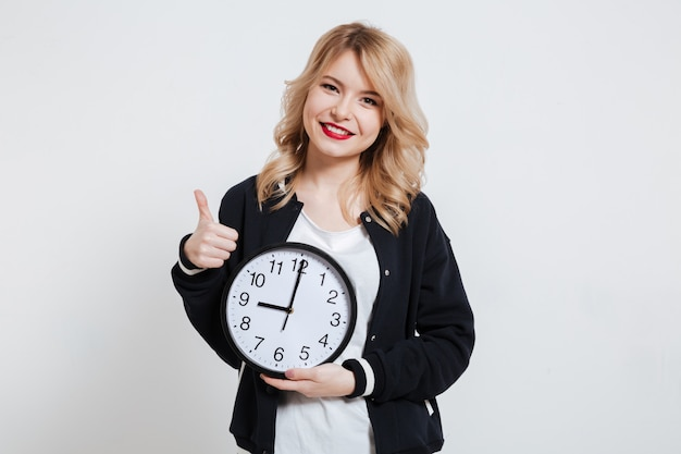 Smiling casual young woman teenager holding clock and showing thumb up