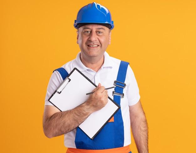 L'uomo adulto caucasico sorridente del costruttore in uniforme tiene la matita e la lavagna per appunti sull'arancia