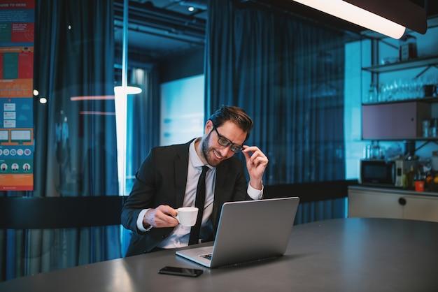 白人のひげを生やした実業家のスーツと眼鏡と新鮮なコーヒーのカップを保持し、会社のキッチンに座ってラップトップを見て笑みを浮かべてください。