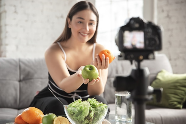 Smiling. caucasian blogger, woman make vlog how to diet and lost weight, be body positive, healthy eating. using camera recording her fruits salad preparing.