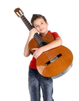 笑顔の白人の少年は、白で隔離のアコースティックギターを保持します