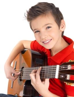 笑顔の白人の少年は、白で隔離のアコースティックギターで遊んでいます