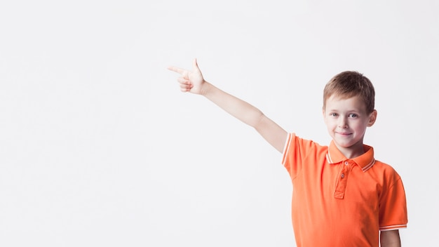Smiling caucasian boy pointing index finger at side on white backdrop