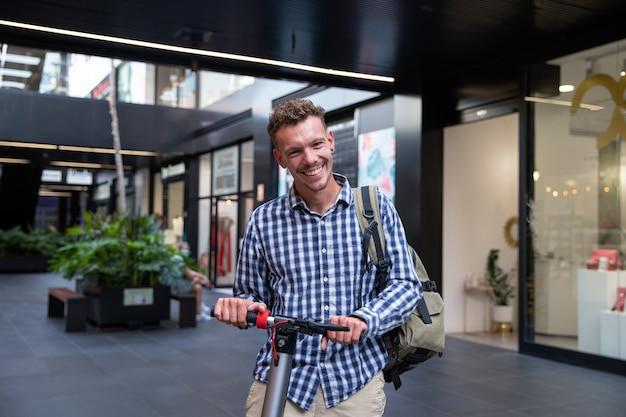 Улыбающийся кавказский мальчик едет на своем электросамокате. случайно одетый мужчина с рюкзаком. устойчивая мобильность и снижение загрязнения