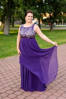 Smiling caucasian brunette woman is touching hem of purple floor-length dress in park.