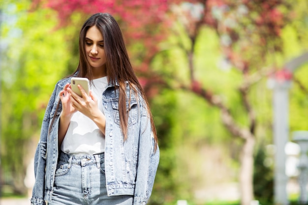 Smiling caucasian brunette young woman sending message on smartphone outside alone wear jeans clothes .technologies and gadgets. advertising for shop selling electricity and mobile phones.