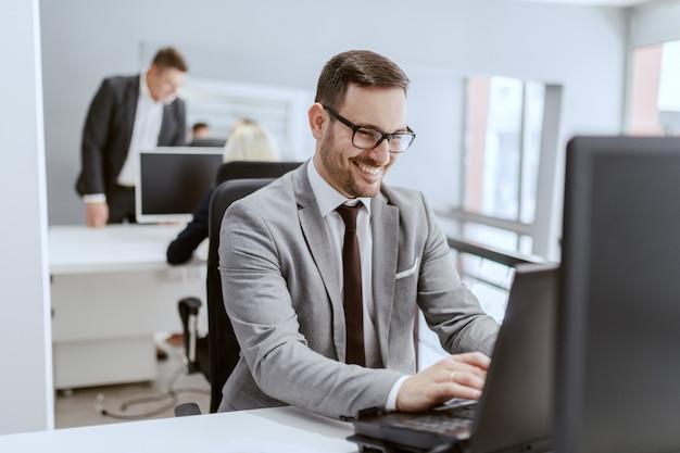 Улыбающийся кавказский бизнесмен в костюме и в очках, сидя на своем рабочем месте и с помощью компьютера, руки на клавиатуре.