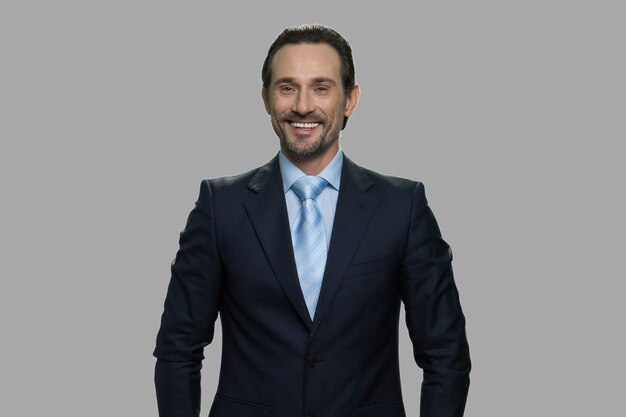 カメラを見て笑顔の白人ビジネスマン。灰色の背景にビジネススーツの陽気な男の肖像画。