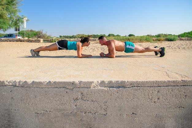 Улыбающаяся кавказская пара делает базовую тренировку на доске