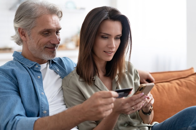 Smiling caucasian couple involved in online shopping, entering payment information from credit bank card in mobile application, satisfied with quick money transfer, modern tech concept.