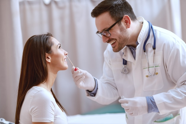 Smiling caucasian doctor taking swab from his patient's nose. clinic interior.
